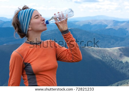 Hiker drinks clear water on top of the mountains - stock photo