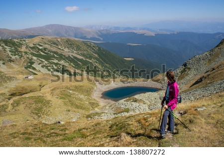 Hiker enjoying the view near a lake in the mountains - stock photo
