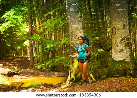 hiker girl standing on a forest road after rain, puddles and mud of.  - stock photo