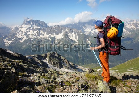 Hiker girl with backpack and ice-axe in a high mountains