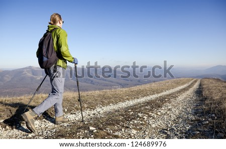 Hiker going over mountain pass. - stock photo