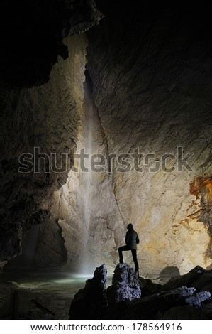 Hiker in a cave, Pissai waterfall, grotta Rio Martino, Italy