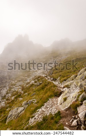 Hiker in Fog Descends from the Top  - stock photo