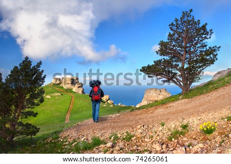 Hiker in mountains over the sea - stock photo