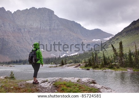 Hiker in Rainy Weather Looking at Mountains - stock photo