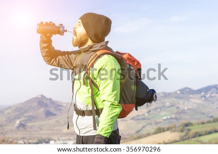 hiker in the mountains drinking water from his water bottle - caucasian people - people, drink and nature concept - stock photo