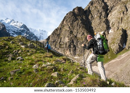 Hiker is climbing mountain in Caucasus mountains in Bezengi region, Kabardino-Balkaria, Russia - stock photo