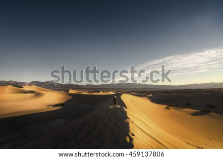 Hiker is hiking on Mesquite Sand Dune in Death Valley National Park, California, USA. - stock photo