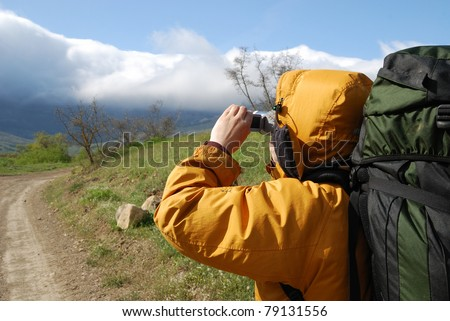 Hiker is shooting a landscape by video camera. He is standing on the natural road. He is carrying a large rucksack. - stock photo