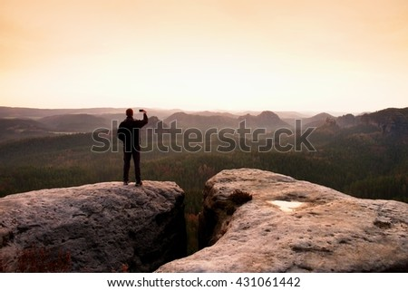 Hiker is taking photo by smart phone on the peak of mountain at sunrise. Selfie mania - stock photo
