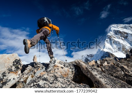 Hiker jumps in Himalaya mountains - stock photo