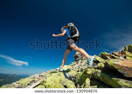 Hiker jumps over stones in Carpathian mountains - stock photo