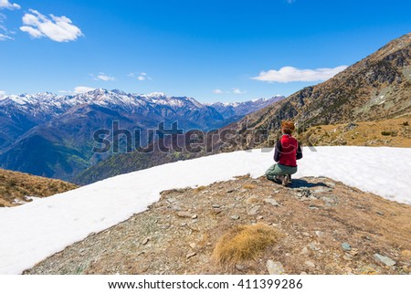 Hiker kneeling and resting on the scenic mountain summit. Expansive view on the snowcapped alpine arc in the background. Rear view, italian Alps in spring.