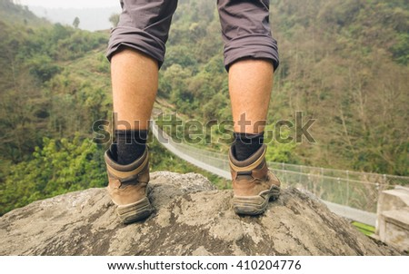 Hiker legs standing on rock above mountain suspension bridge