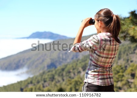 Hiker looking in binoculars enjoying view above clouds during hiking trip. Young Asian woman on hike on La Palma, Canary Islands, Spain. - stock photo
