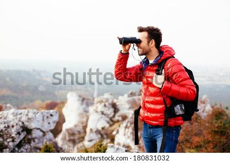 Hiker looking through binoculars - stock photo