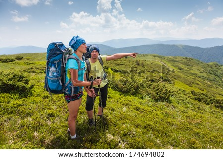 Hiker looks for the way in Carpathian mountains standing far above valley