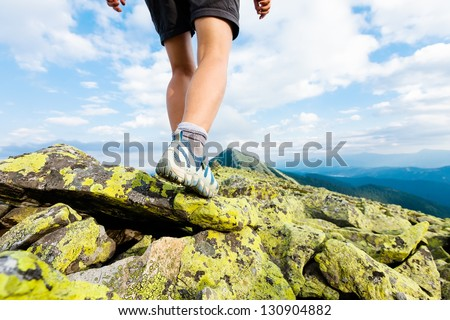 Hiker makes her way over the stones in mountains. Foot closeup - stock photo