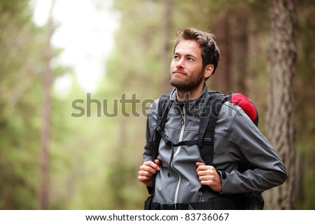 Hiker - man hiking in forest. Male hiker looking to the side walking in forest. Caucasian male model outdoors in nature. - stock photo