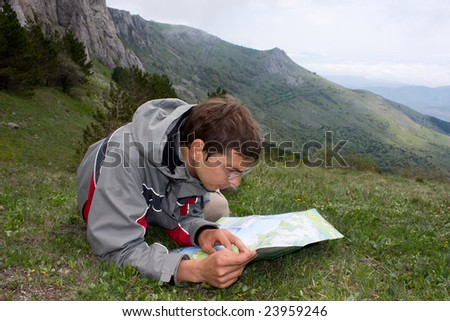 Hiker man laying on grass and looking to the map - stock photo