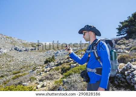 Hiker man using gps for positioning at the mountain - stock photo