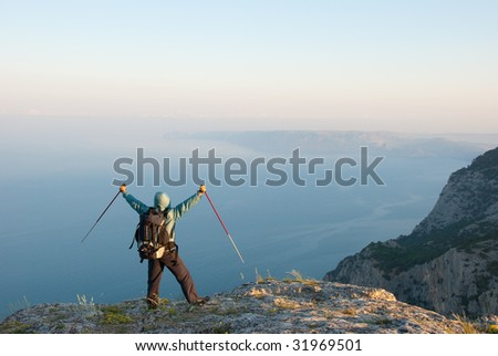 Hiker on a peak enjoys seashore landscape