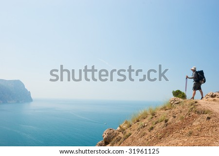 Hiker on a peak looks into the distance - stock photo