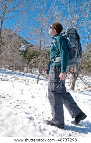 Hiker on a snowy trail, with mountains on a background, Boulder, Colorado, november hike - stock photo
