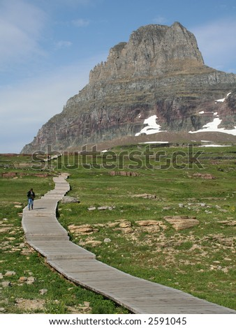 Hiker on Hidden Lake Hiking Trail at Glacier National Park - stock photo