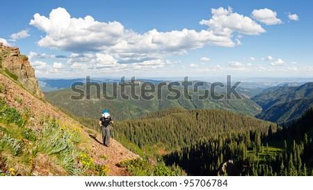 Hiker on the Colorado Trail climbs up to Kennebec Pass in  the San Juan Mountains near Durango, Colorado. - stock photo