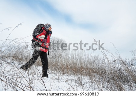 Hiker on the snow on winter field - stock photo
