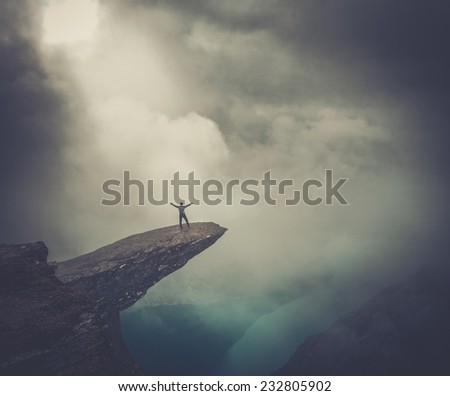 Hiker on Trolltunga with arms wide open - stock photo