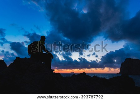 Hiker or runner silhouette backpacker, man looking at inspirational ocean landscape and islands on mountain peak. Accomplished man admire beautiful night and sea. Adventure and lifestyle concept.