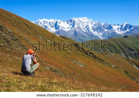 Hiker photographer taking picture of the valley with mountains from view point - stock photo