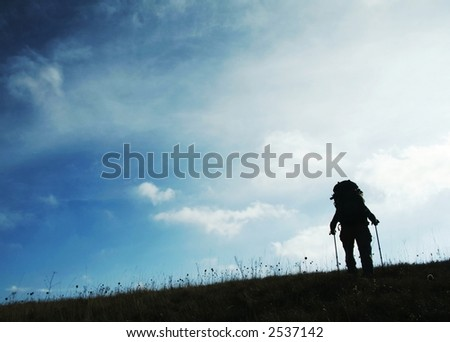 Hiker silhouette on the grassland - stock photo