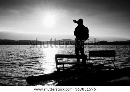 Hiker silhouette with backpack on abandoned  pedal boat in the sunset. Autumn sunny day  at sea