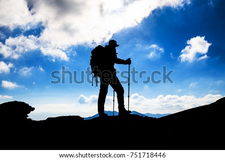 Hiker silhouette with backpack on mountain
