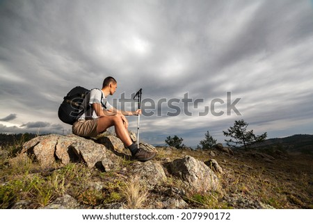 Hiker sits on a rock and looks at the stormy sky