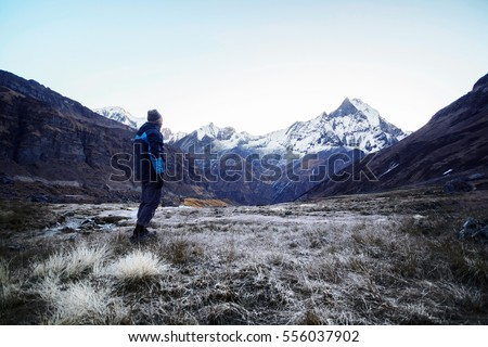 Hiker standing and looking at mountains view in the morning, Annapurna region, Nepal