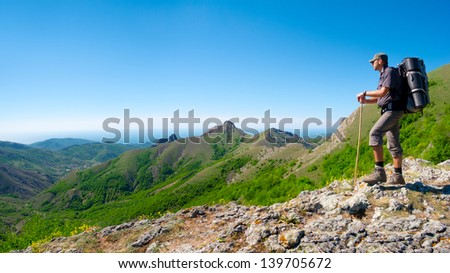 Hiker standing on a stone ridge and enjoys landscape - stock photo