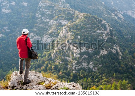 Hiker standing on the rocky edge of one of Pantalica,s canyons in Sicily