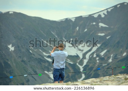 Hiker stands on a peak and enjoy the scenery through binoculars - stock photo