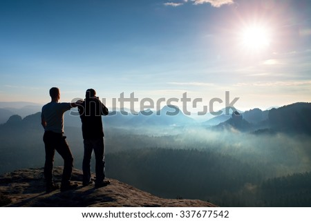 Hiker stay at friend photographer who takes photos of fantastic daybreak in misty moutains. Dreamy fogy landscape, blue misty sunrise in a beautiful valley below - stock photo