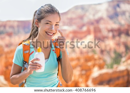 Hiker sunscreen. Woman hiking putting sunblock lotion outdoors during summer hike holidays. Mixed race Caucasian Asian female model. - stock photo