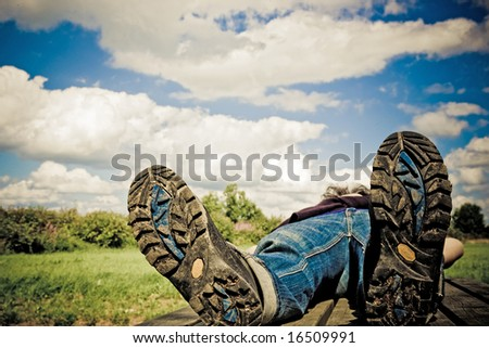 hiker taking a rest on a summer-day.Focus on bottom of hiking-boots.Personal editing velvia filter - stock photo