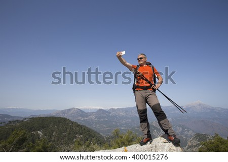 Hiker taking selfie on top of the mountain. - stock photo