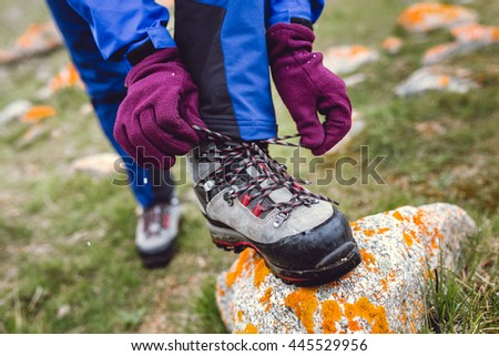 Hiker tying boot laces on rock, high in the mountains