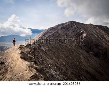 Hiker walking around the rim of Mount Bromo volcano in East Java, Indonesia. - stock photo