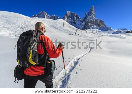 Hiker walking in the snow in the Paneveggio/Pale di San Martino Natural Park. Italy