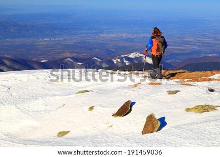 Hiker walks across white snow field on the mountain - stock photo